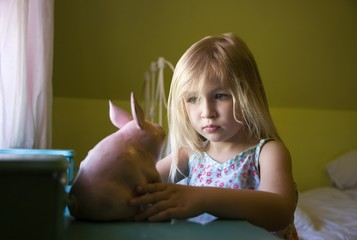 A Girl Looking At A Toy Pig