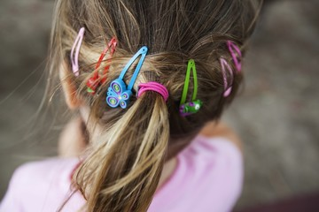 The Back Of A Young Girl's Head Showing Many Hair Accessories In Her Hair; Palm Beach, Gold Coast, Queensland, Australia