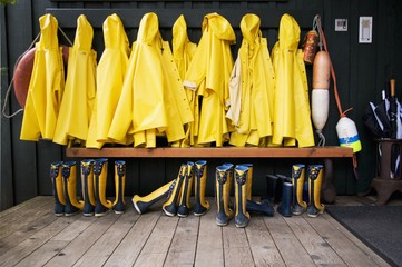 Yellow Raincoats And Rubber Boots Lined Up; Tofino, British Columbia, Canada