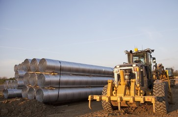 Road Construction Using A Grader And A Bundle Of Culvert Pipes; Edmonton, Alberta, Canada
