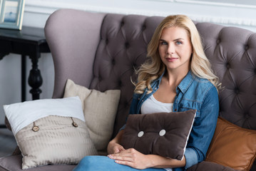 Pretty blond woman sitting on grey couch