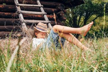 Summer in the countryside - little boy lies near the hayloft