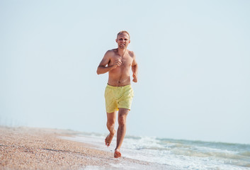 Man jogging on the sea surf line at morning time