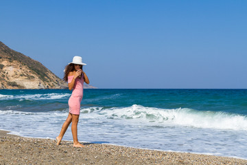 Beautiful carefree woman in short pink dress at the beach.