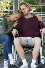 woman hugging man in wheelchair and looking sad
