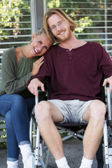 woman hugging young man in wheelchair