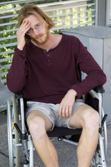 young man in wheel chair looking sad