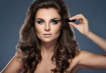 Beautiful woman applying mascara on her lashes