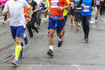 Marathon runners race in city streets, blurred motion