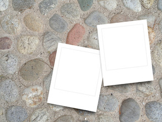 Two square blank photo frames on pebble pavement background