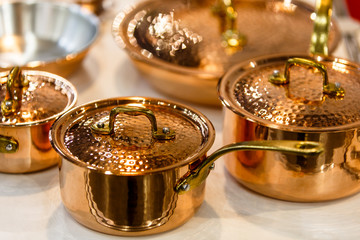Copper cookware, pots and pans are on the counter in the store.