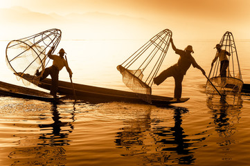 Burmese fisherman on bamboo boat catching fish in traditional way with handmade net. Inle lake, Myanmar (Burma) travel  destination