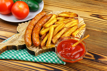 Homemade fast food, portion of french fries, ketchup, grilled sausages, tomato, cucumber on wooden board.