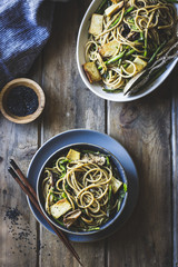 Sesame noodles with tofu and vegetables served on wooden table