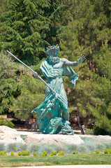 A large public statue of King Neptune that welcomes.
