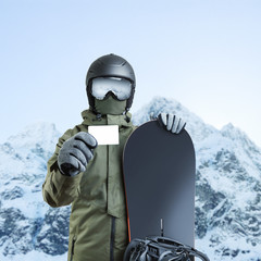 Young snowboarder holding blank lift pass with mountain on background