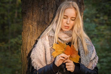 sad girl in autumn park with leaves, toned image