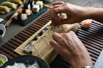 Woman preparing sushi rolls at home