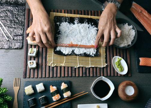 Woman preparing sushi rolls at home