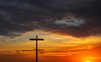 Silhouette of Christian cross over red sunrise or sunset