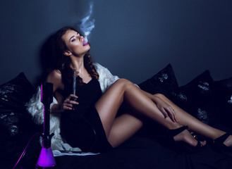 Sexy glamour woman in club dress with long legs smoking hookah.