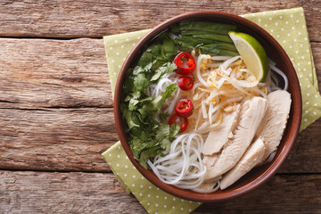 Vietnamese soup Pho Ga with chicken and rice noodles, bean sprouts close-up. horizontal top view