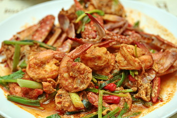 Close up of stir-fried crab and shrimp in curry powder is top-ten of popular Thai food as seafood to fried with  fresh milk ,grill curry ,egg ,oyster oil and yellow curry power. Selective focus.