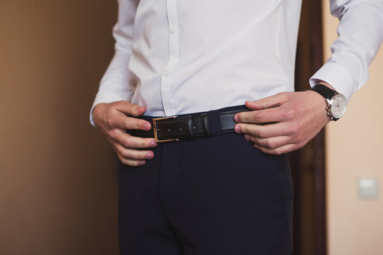 closeup of caucasian man putting on his belt