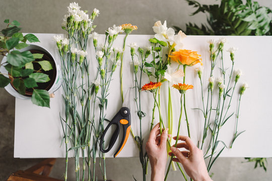Florist workspace: caucasian woman making floral decorations. Top view of flowers and greenery on white wooden table.