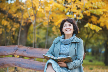 Senior woman is reading the book and dreaming in the park