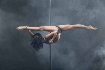 Female pole dancer posing in dark studio Wall mural