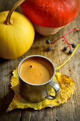 Cup of coffee and pumpkin on wooden background