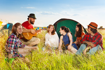 Young people singing to the guitar at campsite