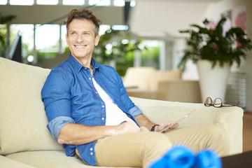 Casual handsome man relaxing at home. Shot a smiling middle aged man relaxing at home on the couch.