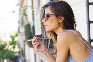 Beautiful young girl in sunglasses smoking cigarette