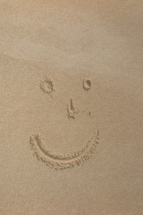 Smile face written in the sand on the beach