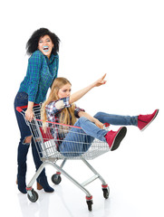 Two happy hipster girls have fun in supermarket's trolley over w