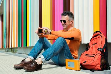 Street fashion. Male outdoor portrait. Man sitting near colored