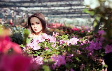 Dreamy woman posing in a garden of flowers