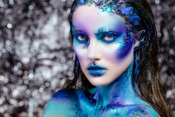 Portrait of a beautiful mermaid girl. Wet skin, wet hair, glitter and scales on his face. Blue eyes. The image on Halloween. Advertising Space.
