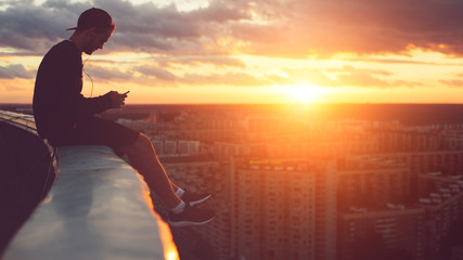 Young risky man chilling above the city with smartphone at sunset