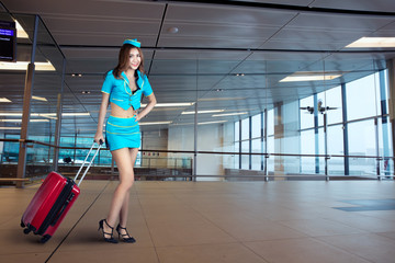 Young air hostess pulling luggage bag in the airport