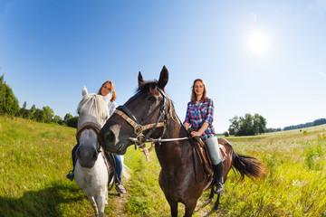 Two female horseback riders mounted on horses
