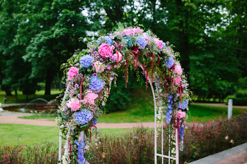 Beautiful wedding arch decorated with pink and golovami flowers outdoors. Wedding concept