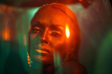 Sparkle of yellow light illuminates beautiful bronze face