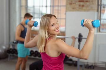 frau trainiert ihre arme und schultern im fitnessstudio