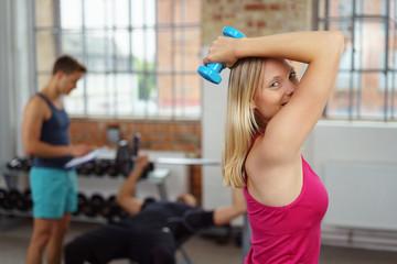 junge blonde frau trainiert mit kleinen gewichten im studio
