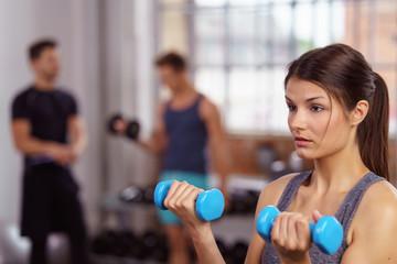 frau trainiert mit gewichten im fitnessclub