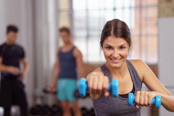 lächelnde junge frau beim fitness-kurs im studio