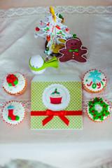 Green Christmas postcad lies between little festive cupcakes
